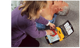 A woman opens an AED to assist a stricken man.