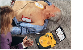 The woman stays well clear of the man as the AED delivers a shock.
